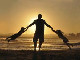 Un père jouant avec ses enfants à la plage