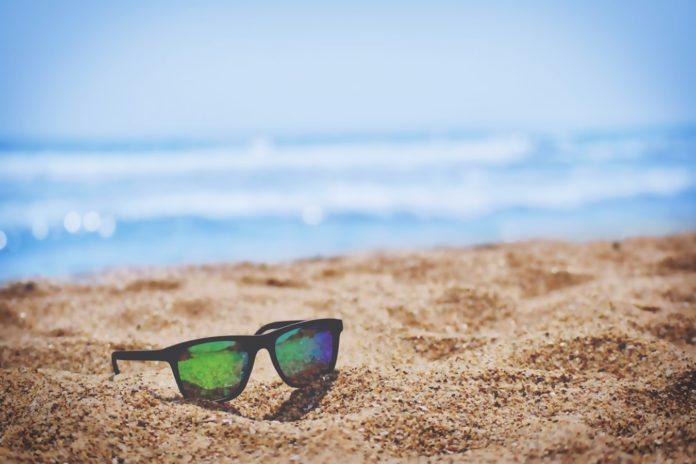 Des lunettes sur le sable d'une plage en été.