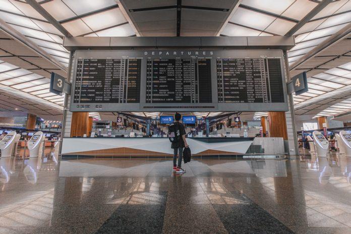 Une passagère consultant un guide de voyage sur un écran, dans un aéroport.