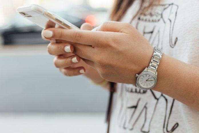 Une jeune femme manipulant son smartphone.
